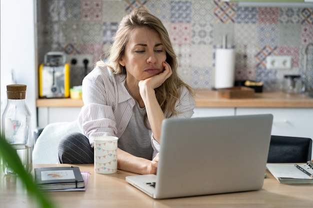 Displeased woman of middle age search for new job unemployed during covid quarantine on laptop