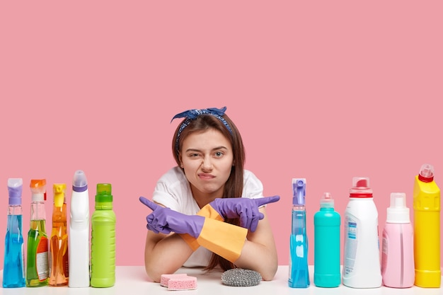 Displeased woman points at different sides, shows cleaning supplies, doesnt like effect, wears purple rubber gloves