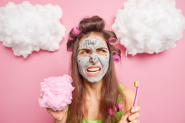 Displeased woman smirks face shows teeth holds toothbrush going to take shower applies clay mask to refresh skin makes hairstyle with rollers undergoes beauty procedures wants to look very beautiful