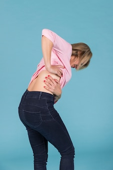 Displeased woman suffering from lower back pain on blue background