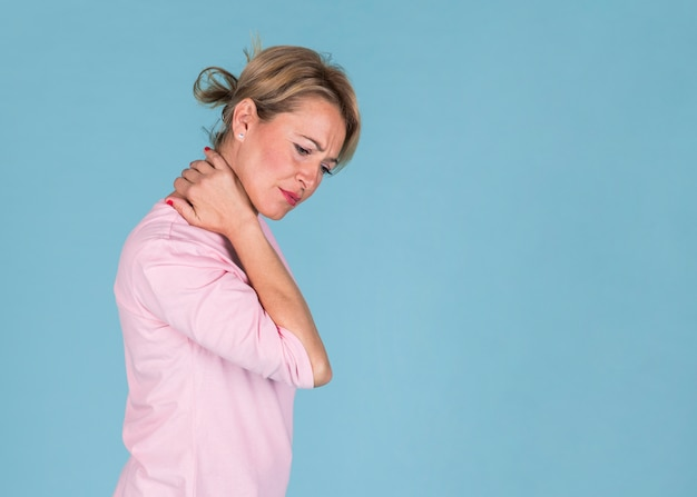 Displeased woman suffering from neck pain on blue background