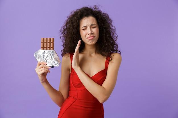 Недовольная женщина в красном платье держит плитку шоколада, стоя изолированно над фиолетовой стеной