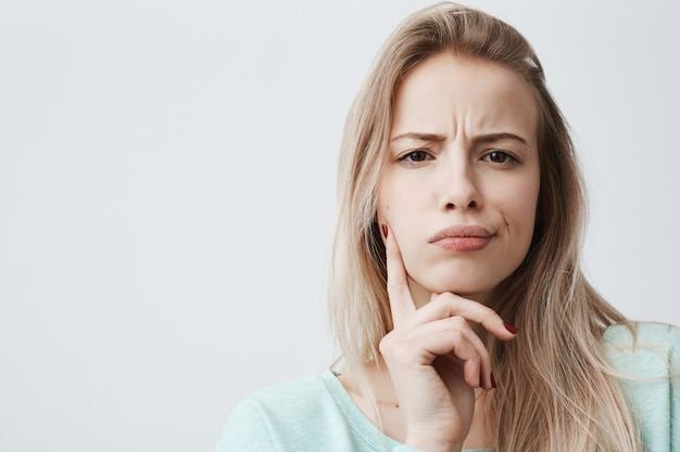 Displeased woman with blonde hair has indignant expression of face, frowns eyebrows, can t understand something. attractive puzzled dissatisfied female keeps hand on chin