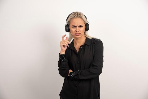 白い背景の上に立っているヘッドフォンで不機嫌な女性。高品質の写真