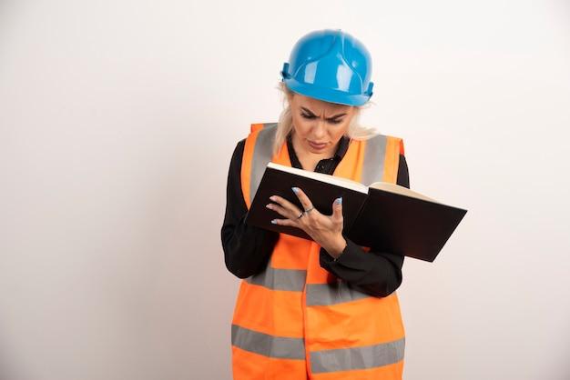 白い背景の上の重要なメモをチェックする不機嫌な労働者。高品質の写真