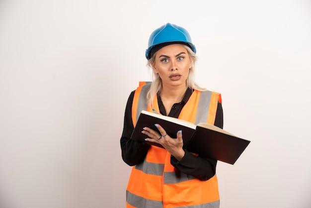 白い背景の上にノートが立っている不機嫌な労働者。高品質の写真