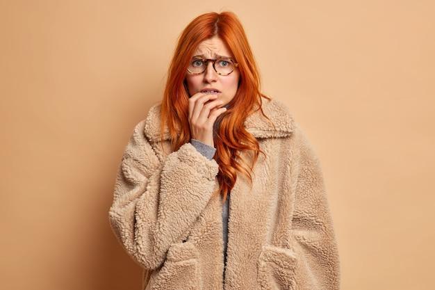 不機嫌な心配赤毛の女性が指の爪を噛むと、暖かい毛皮のコートを着て不安そうに見えます。