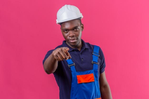 Недовольный молодой афро-американский строитель в строительной форме и защитном шлеме, указывая пальцем с серьезным выражением лица, стоя на розовом