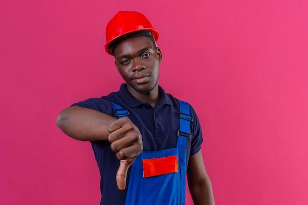 Раздосадованный молодой афро-американский строитель в строительной форме и защитном шлеме показывает палец вниз недовольно стоя на розовом