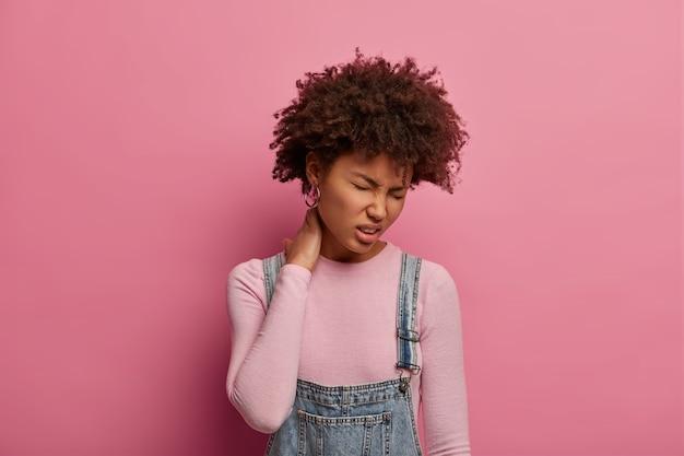 Недовольная молодая афроамериканка чувствует дискомфорт в позвоночнике, трогает шею и хмурится от боли, ведет малоподвижный образ жизни, небрежно одета, позирует на фоне розовой пастельной стены, будучи утомленной.