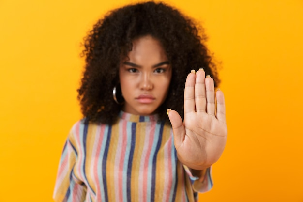 Displeased young african cute girl posing isolated over yellow space make stop gesture.