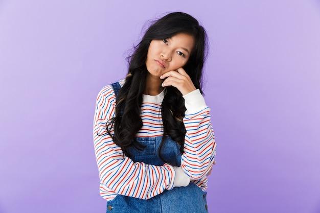 屋内で孤立したポーズをとって不機嫌な若いアジアの美しい女性