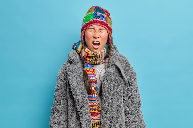 Displeased young asian woman screams loudly keeps mouth opened and closes eyes dressed in warm winter clothing has two pigtails isolated over blue studio wall