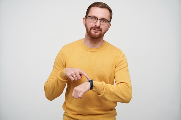 Displeased young attractive bearded male with brown short hair wearing eyewear and pointing on his wristlet watch with pout, standing in casual sweater