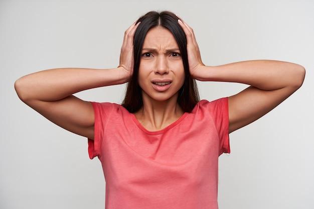 Недовольная молодая привлекательная брюнетка с непринужденной прической, закрывающая уши и хмурящая лицо, пытаясь избежать раздражающих звуков, одетая в розовую футболку