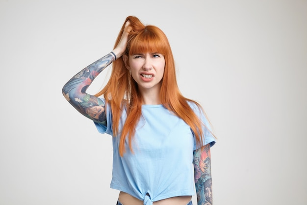 Displeased young attractive redhead tattooed woman clutching her head with raised hand and frowning face while looking aside, isolated over white background