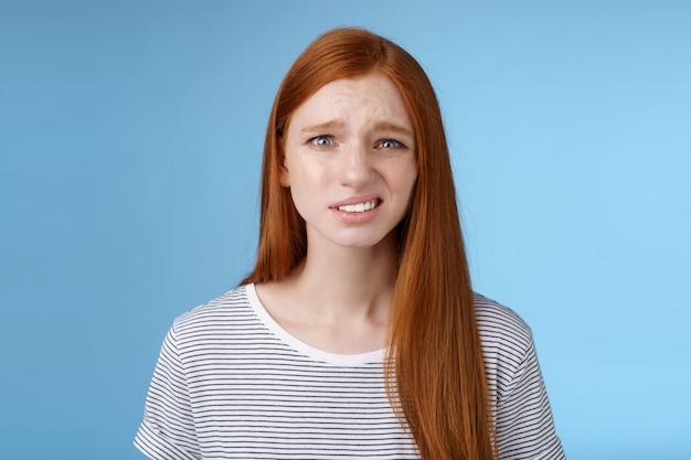 不機嫌そうな若いぎこちない赤毛の女の子は、眉をひそめている眉をひそめている完全な不信感を抱きしめています。コピースペース