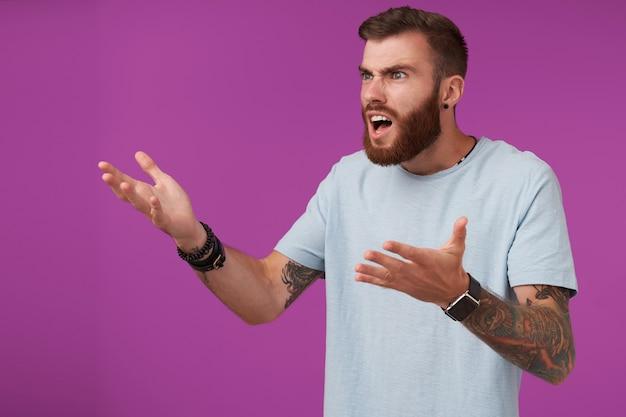 短いヘアカットで口を横に見て混乱して手のひらを上げ、顔をしかめ、紫色でポーズをとっている間口を開いたままにしておく不快な若いひげを生やしたブルネットの男性