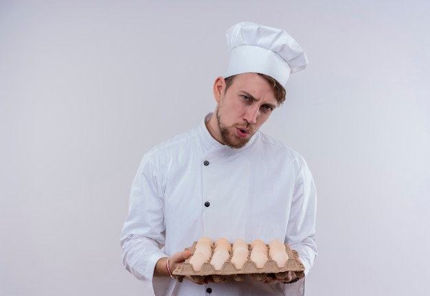 A displeased young bearded chef man wearing white cooker uniform and hat holding a carton of eggs while looking on a white wall