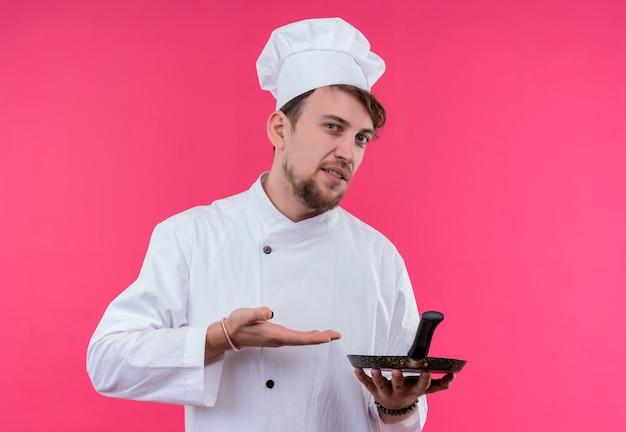 Un uomo giovane chef barbuto scontento in uniforme bianca che mostra la padella mentre guarda su una parete rosa