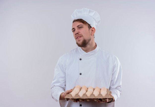 A displeased young bearded male cooker wearing white cooker uniform and hat holding a carton of eggs while looking on a white wall