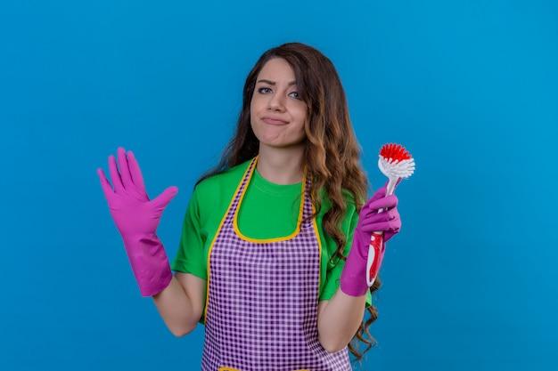 Giovane bella donna scontenta con capelli ondulati lunghi in grembiule e guanti che tengono spazzola per strofinare cercando confuso in piedi con le mani alzate in piedi sul blu