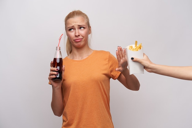 Displeased young blonde female with casual hairstyle looking aside with pout and frowning her face with raised palm, drinking soda and refusing to eat french fries, isolated over white background
