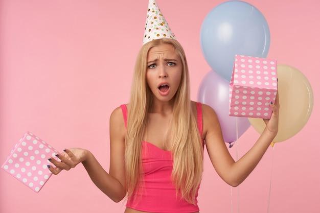 Giovane donna bionda scontenta in top rosa e cappello per le vacanze che riceve scatola regalo vuota, guardando la telecamera delusa e accigliata il suo viso, in piedi su sfondo rosa