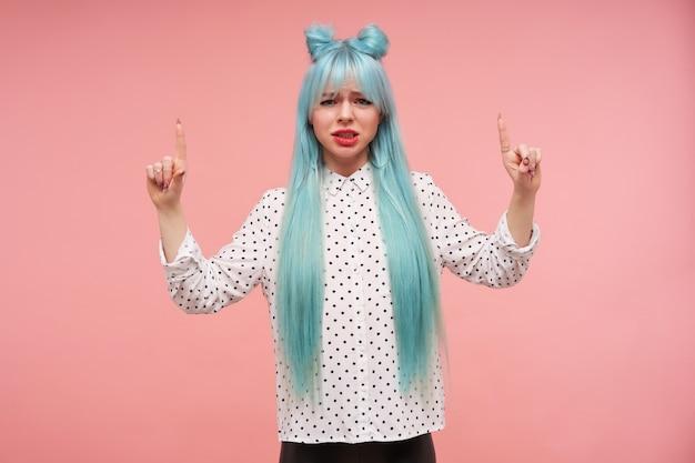 不機嫌そうな若い青い髪の女性は、顔をしかめ、ふくれっ面で見て、人差し指を上げて上を向いて、黒い点のある白いシャツを着ています。