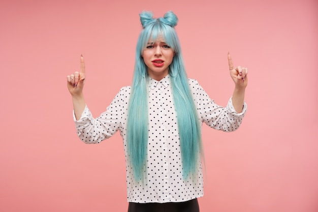 Displeased young blue haired lady frowning her face and looking with pout, raising forefingers and pointing upwards, dressed in white shirt with black dots
