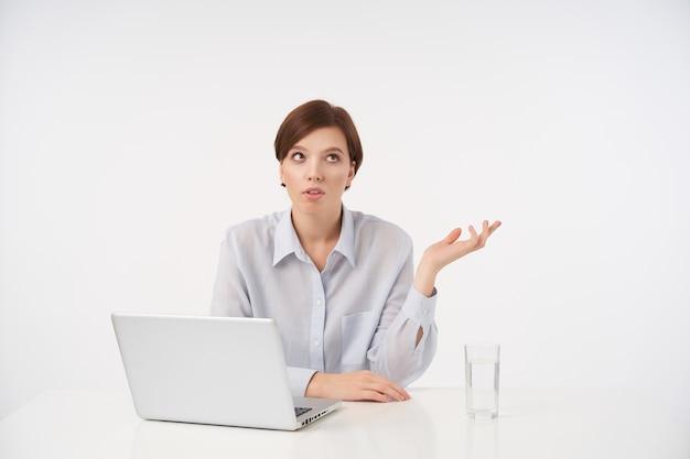 Недовольная молодая кареглазая короткошерстная брюнетка сидит за столом с ноутбуком и смотрит в сторону с надутыми губами, поднимая ладонь, позируя на белом