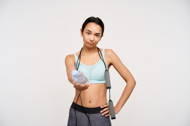 Displeased young brown-eyed slim brunette woman with jumping rope on her neck sharing with someone bottle on water while finishing her training, isolated over white wall