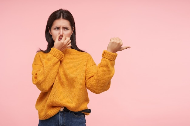 Displeased young brown haired woman dressed in yellow sweater closing her nose with fingers while thumbing aside, standing against pink wall