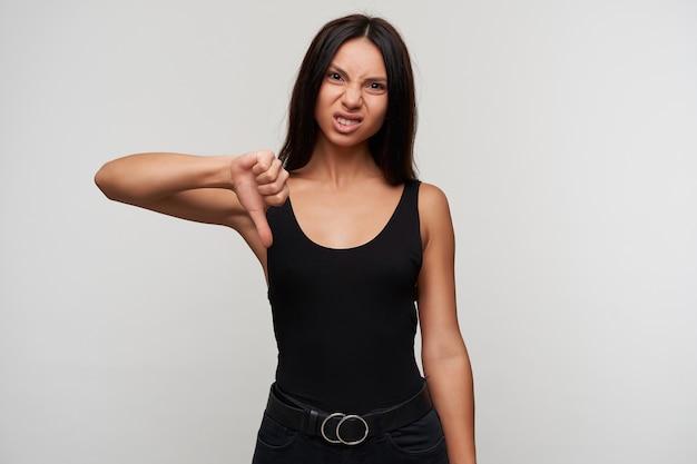 Scontento giovane donna bruna dagli occhi marroni che mostra con il pollice con il broncio e aggrottando le sopracciglia il suo viso, vestito con abiti casual mentre posa su bianco