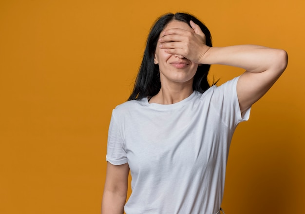 Недовольная молодая брюнетка кавказская девушка закрывает глаза рукой, изолированной на оранжевой стене