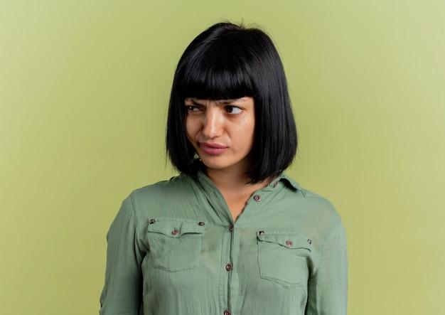 La giovane ragazza caucasica castana scontenta esamina il lato isolato su fondo verde oliva con lo spazio della copia