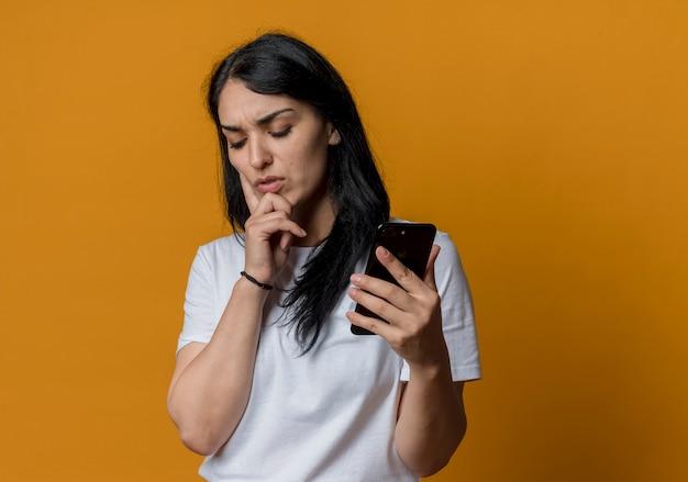 불쾌 하 게 젊은 갈색 머리 백인 여자 오렌지 벽에 고립 된 전화를 들고 턱에 손을 넣습니다.