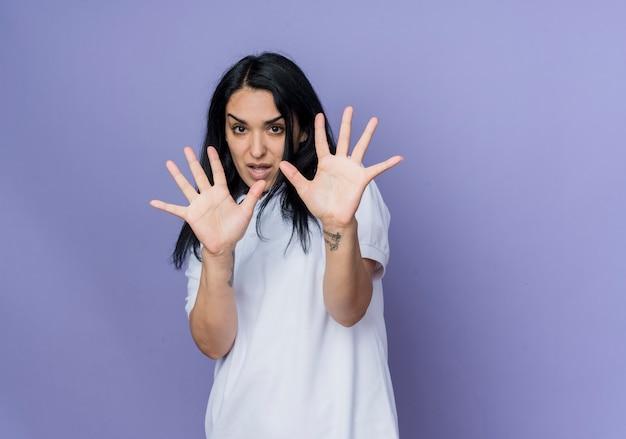 不機嫌な若いブルネットの白人の女の子は、紫色の壁に隔離された手で育てて防御します