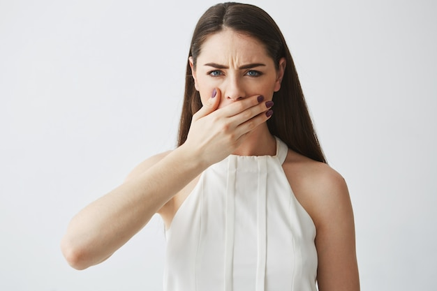 Displeased young brunette girl covering mouth with hand over white backround.