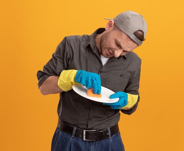 Giovane uomo delle pulizie scontento che indossa abiti casual e berretto in guanti di gomma che tengono piatto e piatto di lavaggio spugna con espressione infastidita in piedi sopra la parete arancione