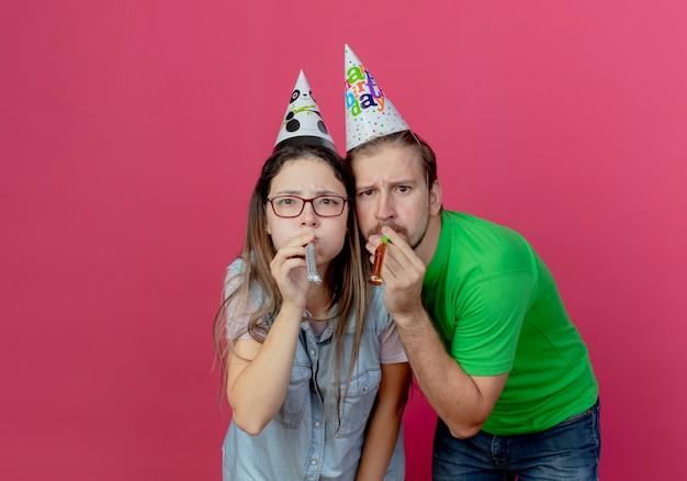 파티 모자를 쓰고 불쾌한 젊은 부부는 서로 분홍색 벽에 고립 된 휘파람을 불고 보인다
