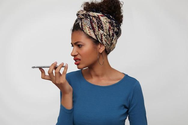 スマートフォンで白い背景の上に立って、不快な電話での会話をしながら彼女の顔を顔をゆがめた若い巻き毛のブルネットの暗い肌の女性を不快にさせる