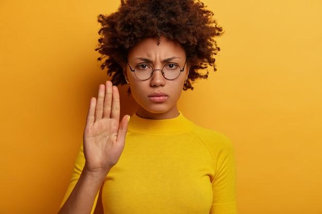 La giovane donna dai capelli ricci scontenta tiene il palmo della mano, fa il gesto di proibire, limita qualcosa, guarda seriamente, indossa gli occhiali, maglione giallo, posa al coperto, ha un'espressione di avvertimento