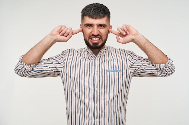 Displeased young dark haired bearded man inserting forefingers in his ears and showing his teeth while grimacing face, isolated over white wall in casual wear