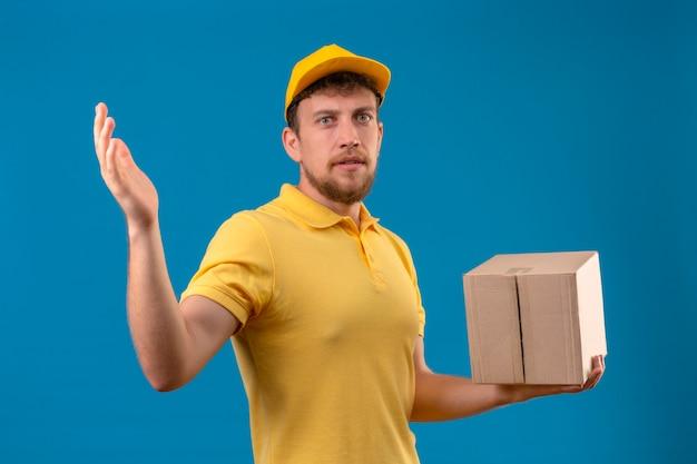 Giovane uomo di consegna scontento in camicia di polo gialla e pacchetto della scatola della tenuta del cappuccio che sta con la mano alzata sull'azzurro