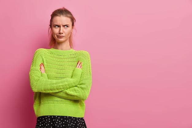 La giovane donna europea dispiaciuta è arrabbiata, tiene le braccia conserte, sorride, si leva in piedi in una posa offesa, indossa un maglione lavorato a maglia verde