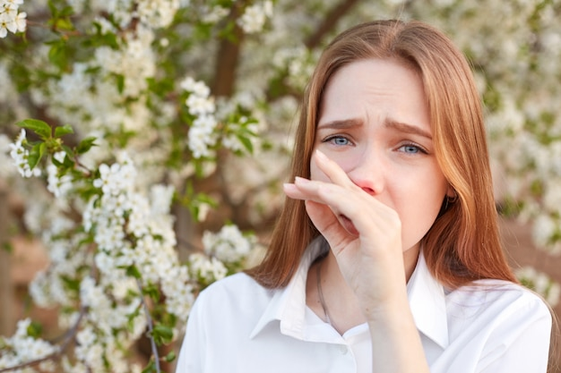 Недовольная молодая женщина имеет насморк, чувствует аллергию на сезонные цветы весной, одетая в белую рубашку, не может ходить на улице