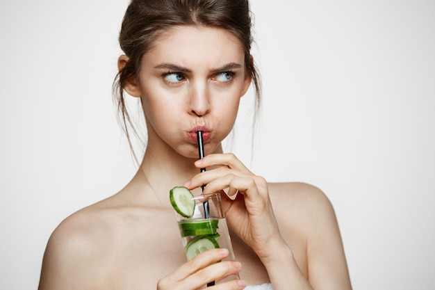 Displeased young girl drinking water with cucumber slices over white background. beauty cosmetology and spa. facial treatment.
