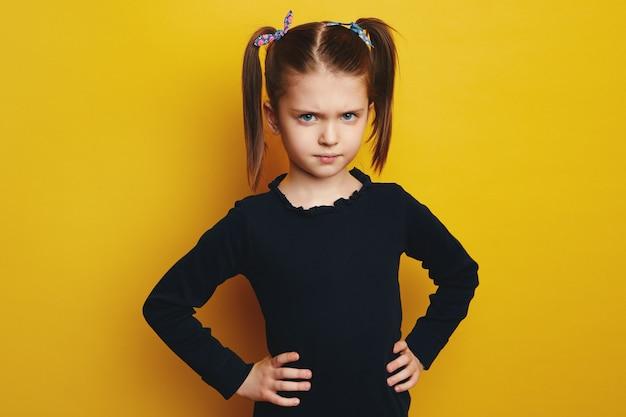 Недовольная молодая девушка хмурится и держит руки на талии над желтым