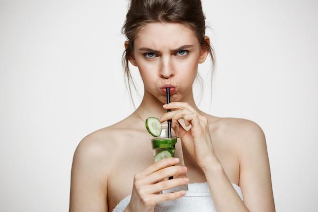 白い背景の上にキュウリのスライスとカメラの飲料水を見て不機嫌な少女。美容美容とスパ。フェイシャルトリートメント。